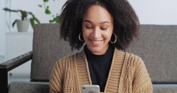 Portré mosolygós afro amerikai nő nézi a telefon mosolygós, tini lány kommunikál barátjával vagy barátaival a közösségi oldalakon online nézi kamera elégedett női arckifejezés