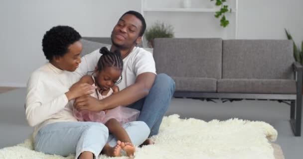 Zwei zärtliche liebevolle Eltern afroamerikanische Mutter und schwarzer Mann sitzen barfuß auf dem Boden mit einem kleinen Mädchen in rosa Kleid, junges Paar mit Tochter plaudert zu Hause, liebevolle Familie hat Ruhe