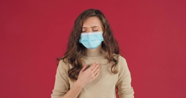 Studioporträt einer kaukasischen Frau mit medizinischer Maske auf dem Gesicht, die an Bronchitis leidet, Asthma Coronavirus spürt Symptome einer koviden Lungenentzündung und steht isoliert auf rotem Hintergrund