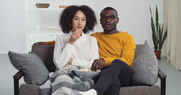 Fiatal afro-amerikai tini pár fekete férfi és etnikai nő család néz film ül a kanapén otthon borított takaró eszik popcorn megvitatása TV-műsor beszélő párbeszéd közeli