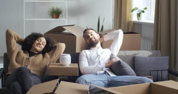 Multiethnisches Paar afroamerikanische Mädchen Frau und kaukasischer Mann Mann sitzt auf Sofa im Wohnzimmer in der Nähe von Kartons ruhen müde Erschöpfung von starken Anstrengungen während des Umzugs