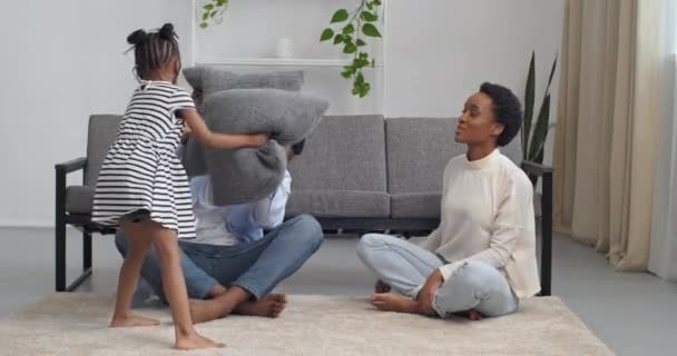 Happy mixed ethnicity family mom african dad and little kid girl having fun with grey pillow fight on floor in living room young interracial father with daughter laughing feel joy play funny game