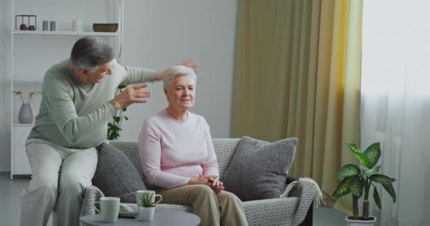Starší žena šedovlasá hospodyňky sedí na gauči trpí bolestí v krku křeče zad milující aktivní starý muž manžel vejde do moderního obývacího pokoje vlny jeho ruce dělá jeho milovanou dámu masáž