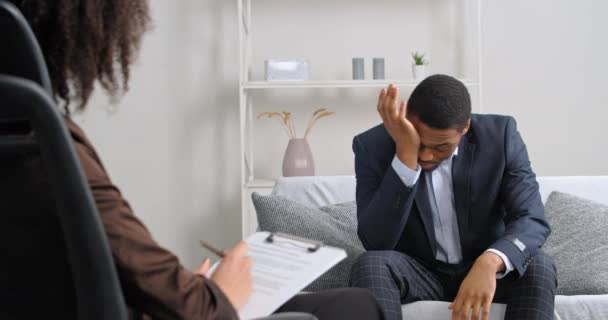 Afro american sad business men worried about divorce dismissal problems feeling stress holding his head with hands telling doctor woman psychologist needs help weekly session psychiatrist consultation