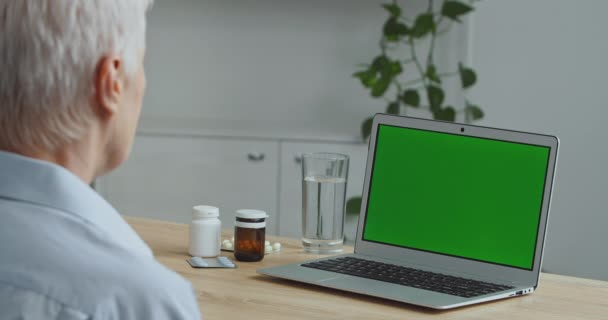 Close-up view from behind gray-haired unrecognizable old woman grandmother sick patient looks at green screen modern laptop sits at table with bottle of pills medicine uses online technologies at home