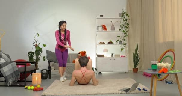 Paar trainiert zu Hause im Wohnzimmer umgeben von Sportgeräten Mann trägt Retro-Trainingsanzug liegt auf dem Boden hebt seine Hüften und Beine in die Luft und macht akrobatisches Element, während Trainerin steuert hilft