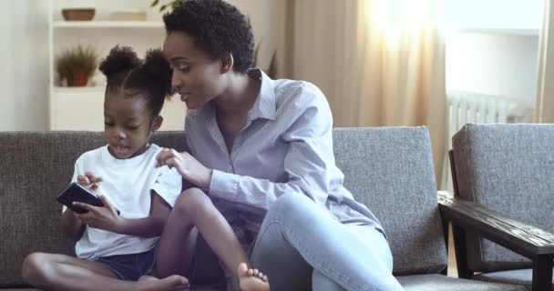 Curly African American mother and little girl sitting at home sofa. Woman showing something to small cute daughter on smartphone screen. Mom with little kid tapping, scrolling playing on mobile phone