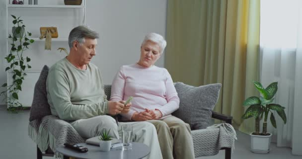Caucasian family old couple elderly man pulls out banknotes from wallet counts dollars gives money to his beloved wife mature woman enjoy successful financial affairs salary at home, savings concept