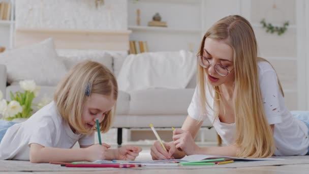 Fürsorgliche Mutter blonde Frau ältere Schwester Babysitter Hauslehrerin Mutter auf dem Boden liegend mit kleinem Mädchen Tochter hilft Baby Bild auf Papier zeichnen mit Bleistiften, Familie Zeichnung zusammen am Wochenende