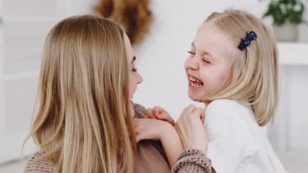 Portré szőke kaukázusi nő boldog anya dadus bébiszitter ölelés kislány baba aranyos lány csiklandoz ölelés csókok arc gyermek játék játék otthon, gyerek nevet őszintén hangosan csiklandozás