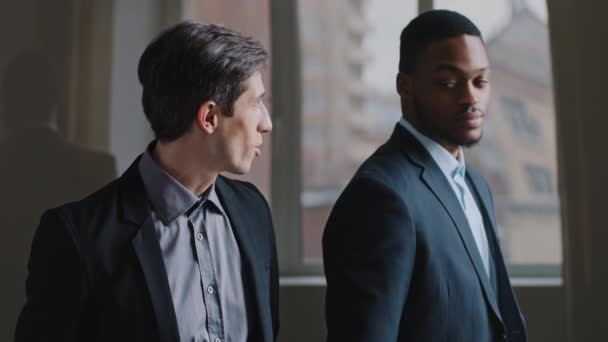 Dva kolegové stojí v moderní kanceláři společnosti vyhlédnout z okna, šťastný běloch obchodní muž mluví body směr s ukazováčkem mimo šéf africký etnický vůdce manažer přikyvuje ano