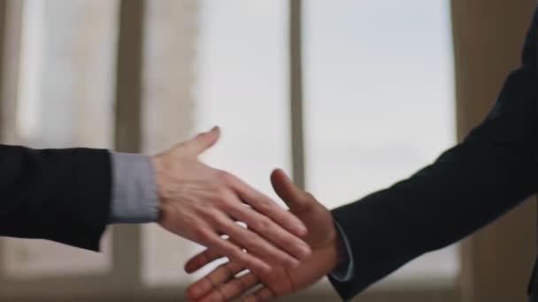 Detailní záběr mužské dělníky ve formálních oblecích dělat neobvyklé legrační potřesení rukou neformální stání v úřadu na pozadí okna gesto úspěchu spolupráce znamení jednoty znamení