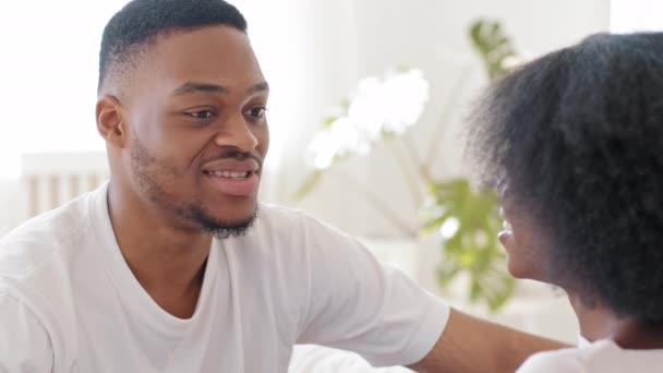 Portrait african man ethnic black guy chatting talking speaking with unrecognizable woman with afro hairstyle curly hair unknown mixed race girl sitting home indoors casual conversation communication