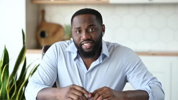 Inline schůzka. Přátelsky sebevědomý úspěšný mladý africký vousatý muž, výkonný ředitel, na volné noze nebo konzultant, mluví během videokonference s kolegy nebo zákazníkem, gestikuluje rukama, usmívá se