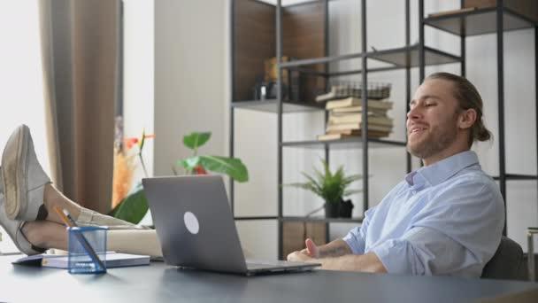 Lächelnder attraktiver junger Mann, Freiberufler oder Manager, entspannt am Arbeitsplatz mit auf den Tisch geworfenen Beinen. Moderner Typ benutzt Laptop, chattet per Videokonferenz mit Kollege, gestikuliert mit den Händen