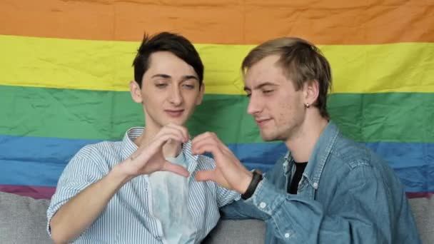 Homosexual gay couple in love. Guys kissing and showing heart symbol with hands, against lgbt colorful rainbow flag, they are happy to be together. Love is love