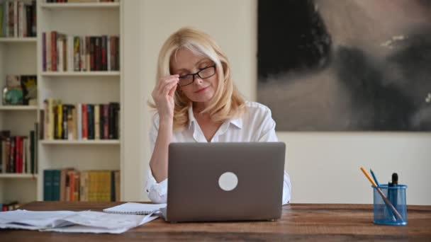 Fáradt ideges kaukázusi érett szőke, vezérigazgató, menedzser vagy szabadúszó, fehér ing, fáradt online munka laptop, tapasztalt stressz, dörzsöli a szemét a kezével, fejfájás, migrén, szüksége van pihenésre