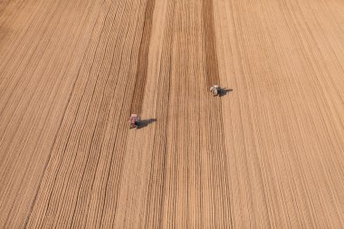 Harvest fields with tractors
