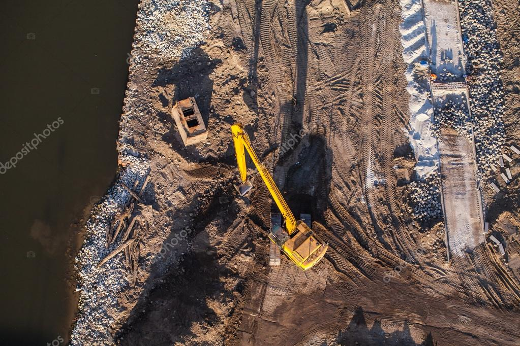 Long arm excavator working on river bank