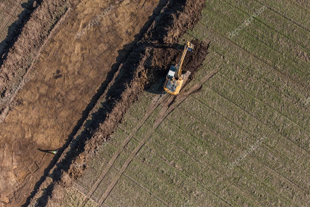 Long arm excavator working on the field