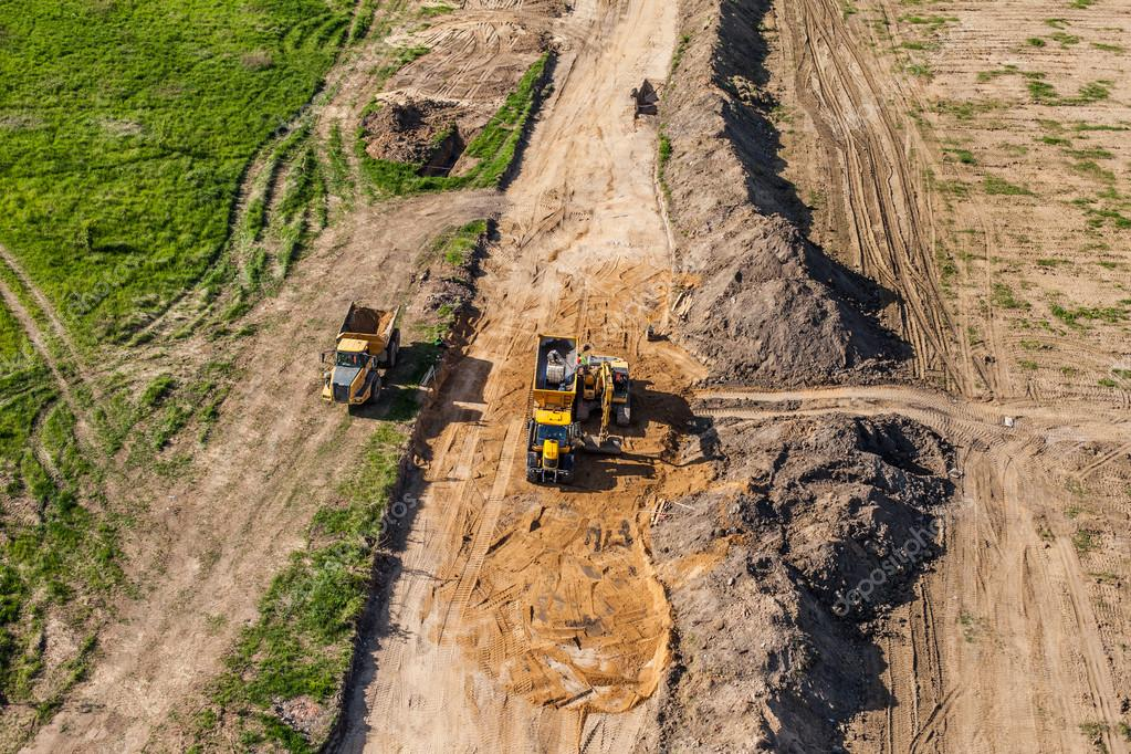 aerial view of long arm excavator working on the field