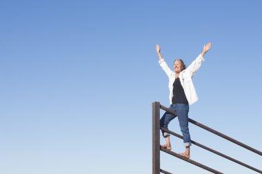 Joyful mature woman with arms up outdoor