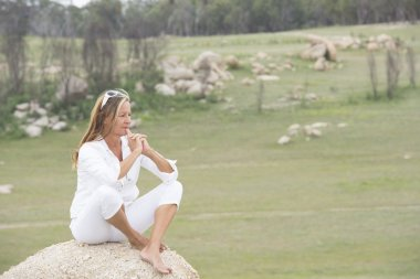 Thoughtful woman outdoor sitting on rock