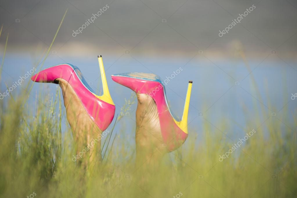 Peaking out high heel shoes in field of high grass