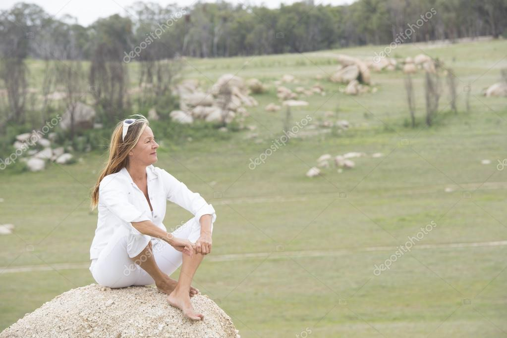 Happy relaxed woman outdoor sitting on rock