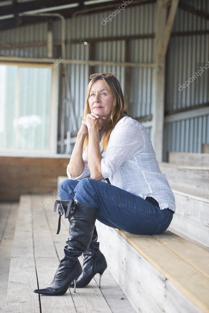 Thoughtful mature woman in jeans and high heels