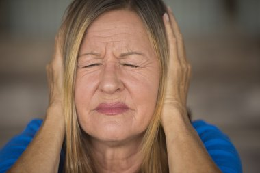 Stressed woman pain from loud sound