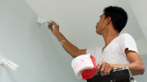 Asian man painting house