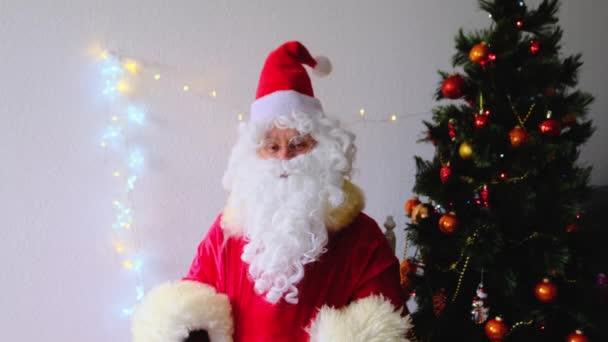 idős Mikulás fehér szakállal gratulál a gyerekeknek és a felnőtteknek, bankjegyeket tart a kezében, ad nekik, összpontosít a pénzre, koncepció a karácsony, üdülési kedvezmények, vásárlás, ajándékok