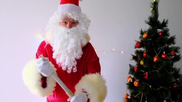 idős Mikulás fehér szakállal gratulál a gyerekeknek és a felnőtteknek, kezében egy evező, koncepció a karácsony, nyaralás vásárlás, ajándékok, gratulálok