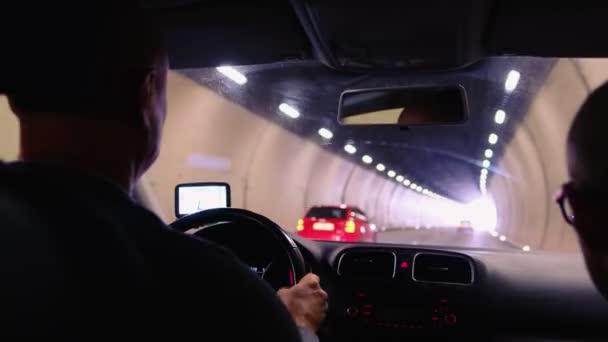 řidič auta projíždějící dlouhým osvětleným tunelem ve švýcarských horách, selektivní zaměření na palubní desku vozidla, koncepce automobilové dopravy, pozitivní výstup, silniční doprava