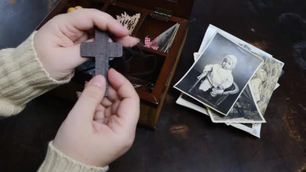 female hands are sorting dear to heart memorabilia in an old wooden box, a stack of retro photos, vintage photographs of 1960, concept of family tree, genealogy, connection with ancestors