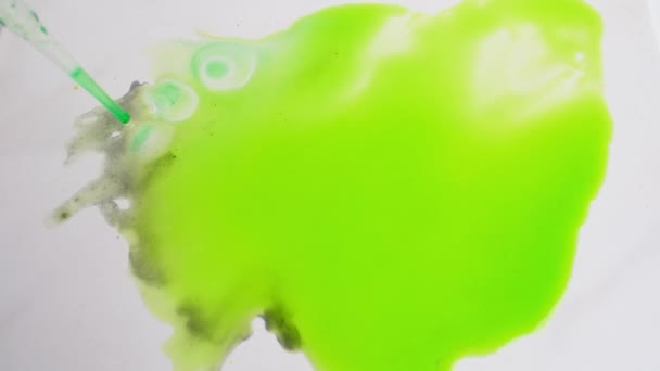 abstract spots of green paint spread over a white surface, drawing with watercolors, alcohol ink, background for a designer, art therapy
