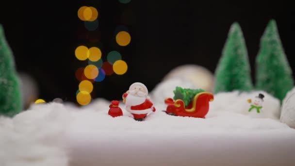 Vánoční hračka na pozadí věnce. Hračky Santa Claus na pozadí žárovek. Vánoční pozadí Santa Claus s dárkem.