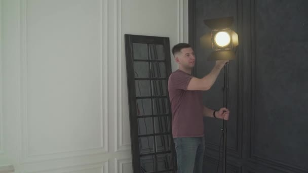 Lighting man placing a sheet of diffuser on a studio light in a Television studio. The illuminator puts the light on the rack in the studio. little men puts light on the set