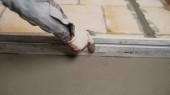Der Arbeiter nivelliert die Wand mit Draht. Der Bauherr reibt den nassen Mörtel ab. Legen Sie den Mörtel an die Wand. Renovierung zu Hause. Putzfrau verteilt Putz auf Wand.