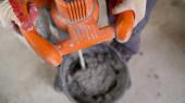 Der Arbeiter mischt den Mörtel. Nasse Beton- oder Motrar-Mischtextur. Graumörtel, Betonoberfläche. Die Lösung ist angerührt, Wohnungsrenovierung.