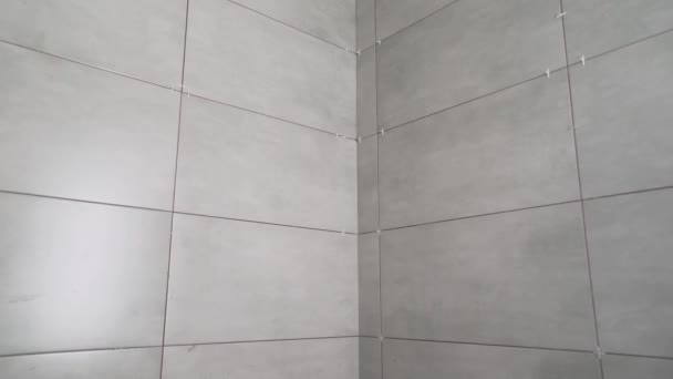 New dark tiles in the bathroom. Empty modern bathroom with gray tiles. Black tiles on the wall.