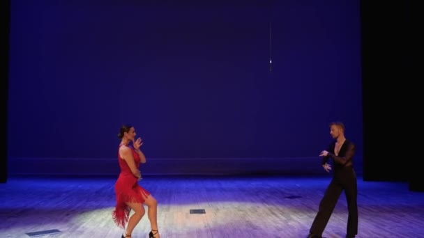 A girl in a red ball gown and a guy in a black bodysuit. Dance moves against a bright background indoors. Elegant dancers, ballrom dance on theatre stage. Ballroom couples dance on stage.