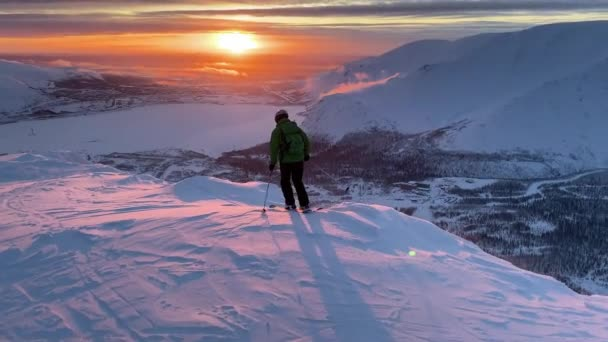 Ein Mann fährt auf einem Bergrücken in den Strahlen der untergehenden Sonne