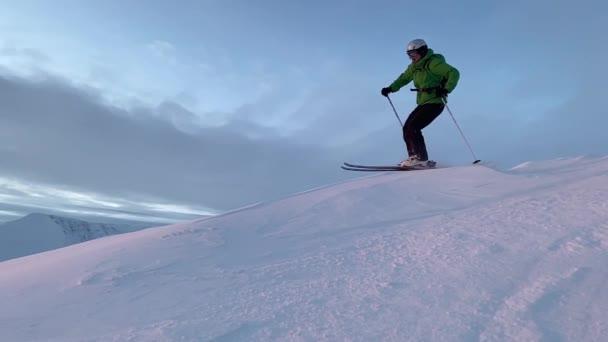Ein Mann fährt in den Strahlen der untergehenden Sonne auf einem Bergrücken Ski. Zeitlupe.