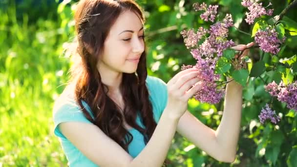 young beautiful woman in the blossoming spring garden Lilac