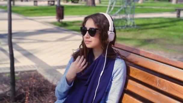 fiatal nő napszemüveg zenehallgatás fejhallgató a parkban egy padon