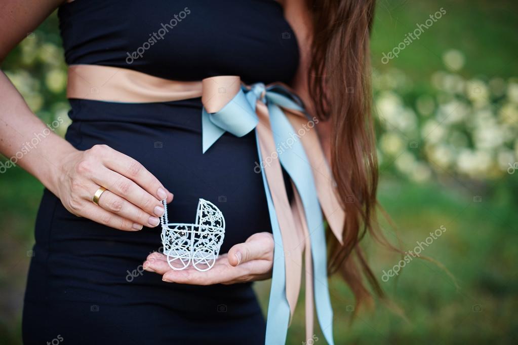 Terhesség koncepció  has és kézi üzem kis játék babakocsi előtt a rózsaszín  háttér — Stock dbd3082d25