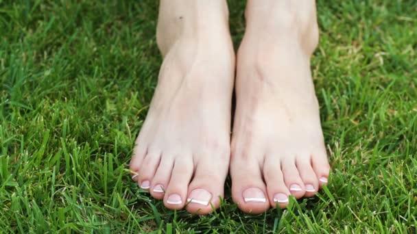 Primo piano di un piedi femminili con il bianco french pedicure sulle unghie