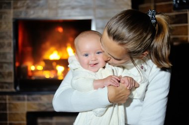 mother with her baby near the fireplace at home